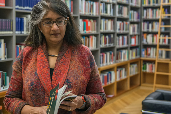 Shalini Randeria, wearing a red jacket, is standing in the IWM library holding a book.