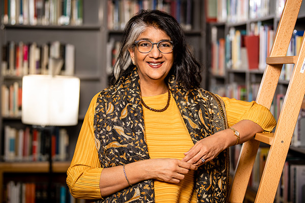 Shalini Randeria in a yellow top leans on the library ladder in the IWM library, surrounded by books